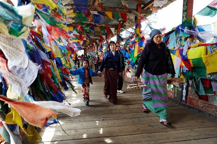 Un groupe de femmes passe devant les drapeaux de prière aux tons colorés de Thimphou, la ...