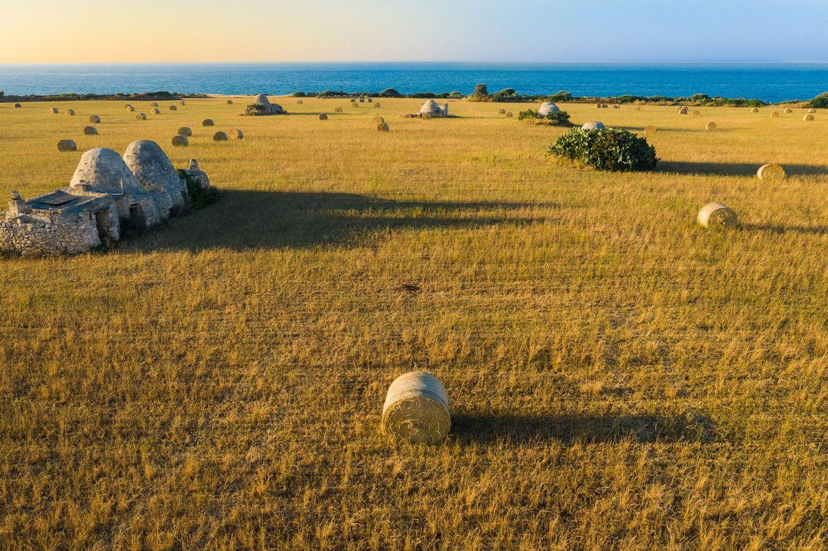 Des bottes de foin constellent ce champ de blé moissonné à Polignano a Mare, une ville ...