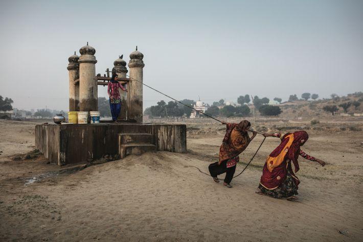 Des femmes s'efforcent de tirer l'eau d'un puits, à Dongra, au Rajasthan, un État désertique. De tels puits ont ...