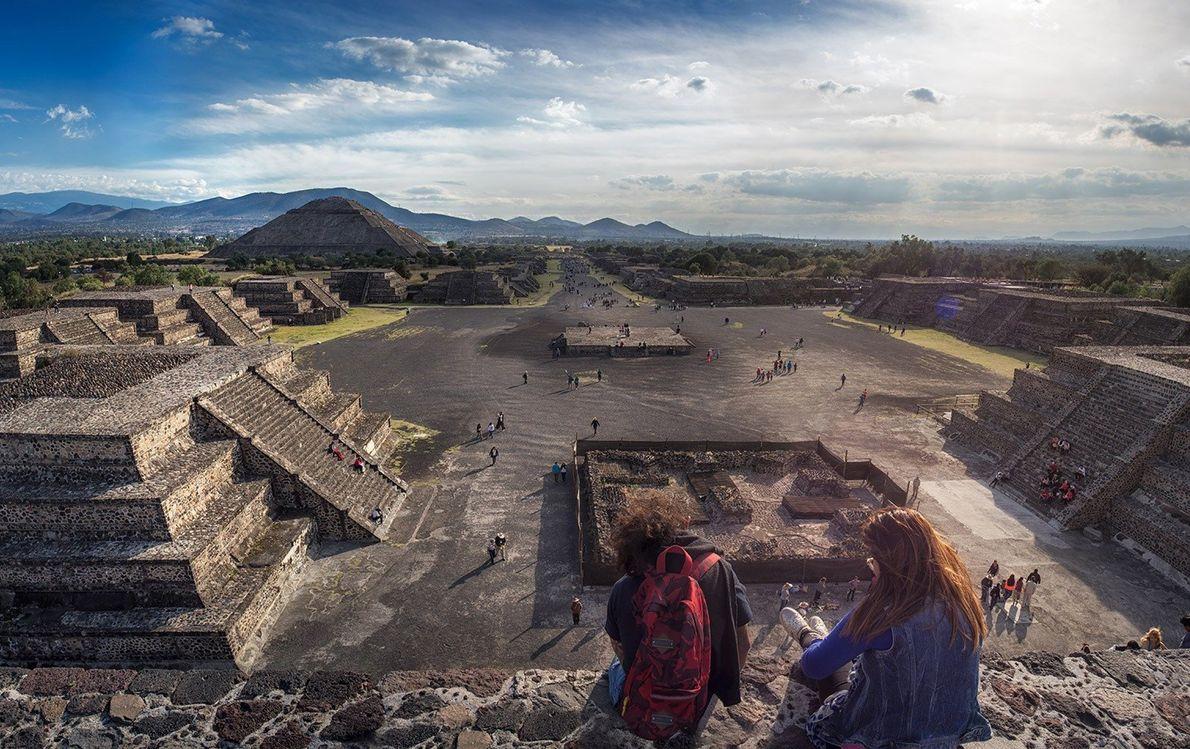 Des voyageurs font pendre leurs jambes depuis le sommet d'un temple qui surplombe Teotihuacán, une ancienne ...