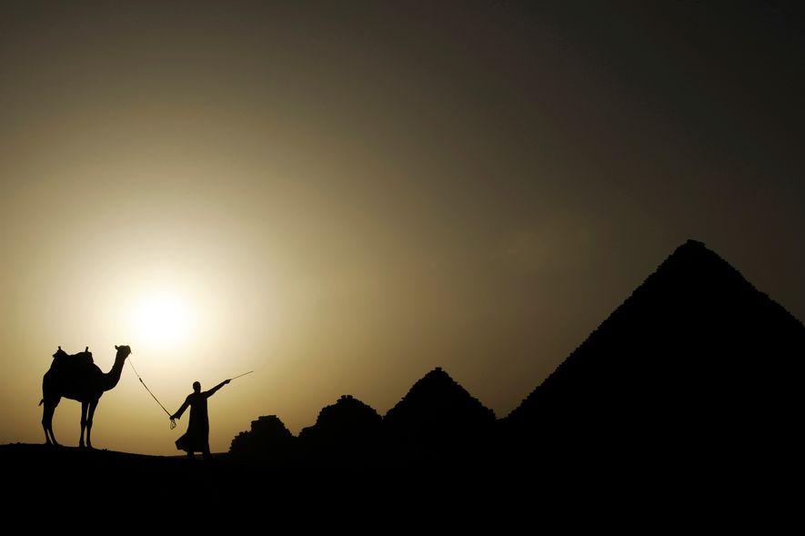 Le soleil se couche sur la nécropole de Gizeh, à la périphérie du Caire, en Égypte.