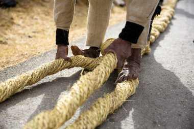 Un homme tresse de la corde fraîche pour former des câbles épais qui seront utilisés comme ...