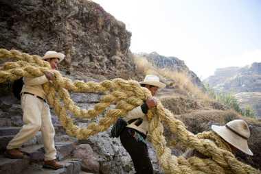 Des hommes participant à la cérémonie transportent la longue et lourde corde dans le canyon pour ...