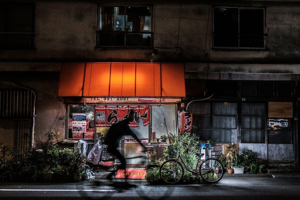 Un cycliste passe devant la boutique aux couleurs chaleureuses d'un vendeur de nouilles à Nakano, un ...