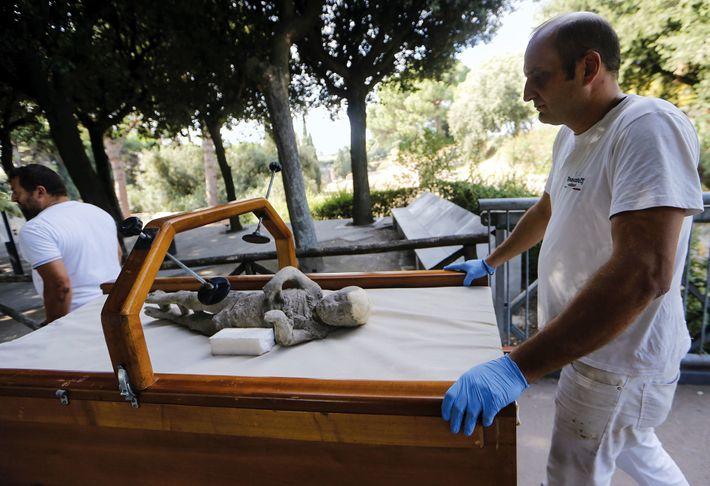 Des travailleurs portent la dépouille d'un jeune Pompéien afin de la soumettre à une analyse ADN. ...
