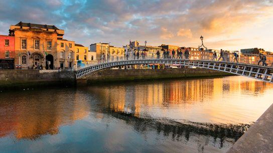 Les rayons dorés du soleil illuminent Ha'Penny Bridge à Dublin, en Irlande.