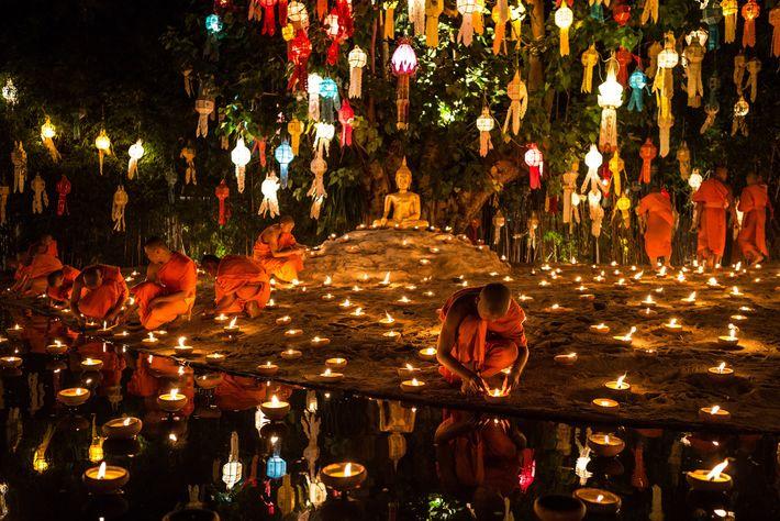 Des moines allument des bougies en préparation de la fête de Loi Krathong qui se tiendra ...