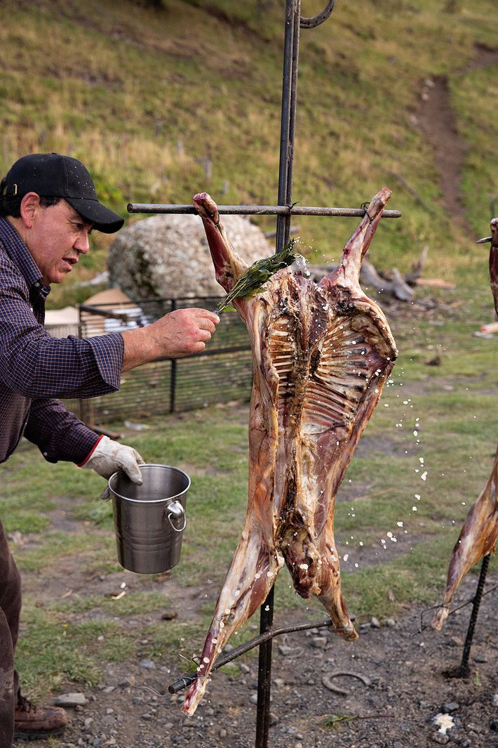 Un agneau en train d'être fumé est badigeonné de coriandre et d'eau, afin d'éviter qu'il ne ...
