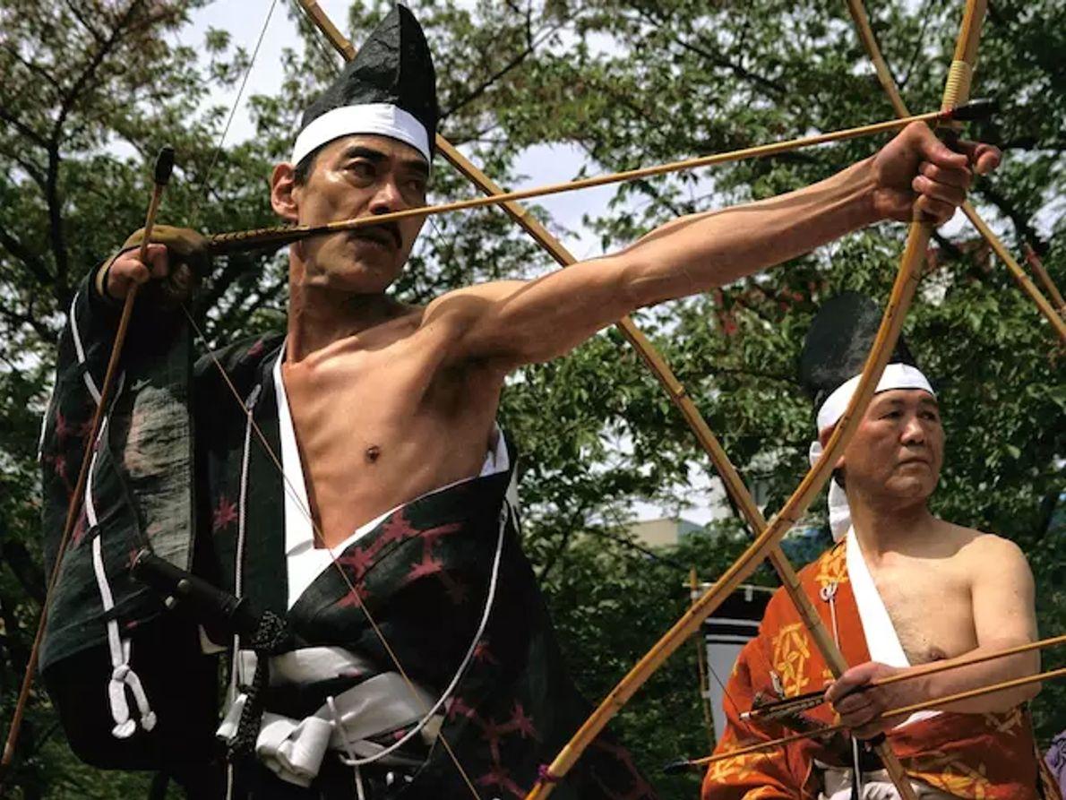 Avec l'intensité d'un samouraï, un homme bande son arc lors d'une compétition de kyudo, ou tir à l'arc, ...