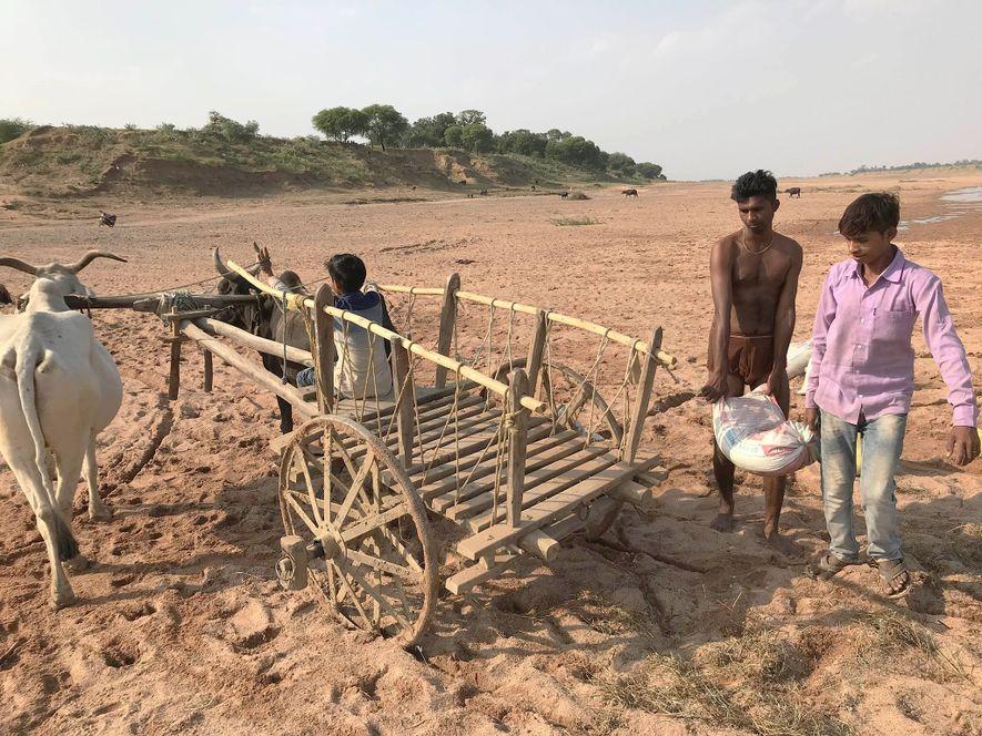 Deux mineurs artisans chargent leur charrette sur la rivière Ken dans le nord de l'Inde.