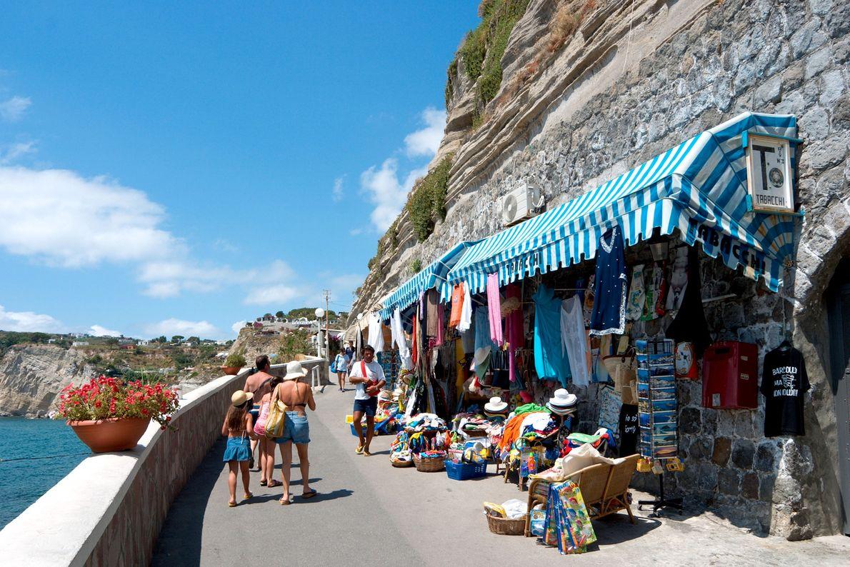 Les touristes flânent sur les rues côtières dans le village voisin de Sant'Angelo, où tout le ...