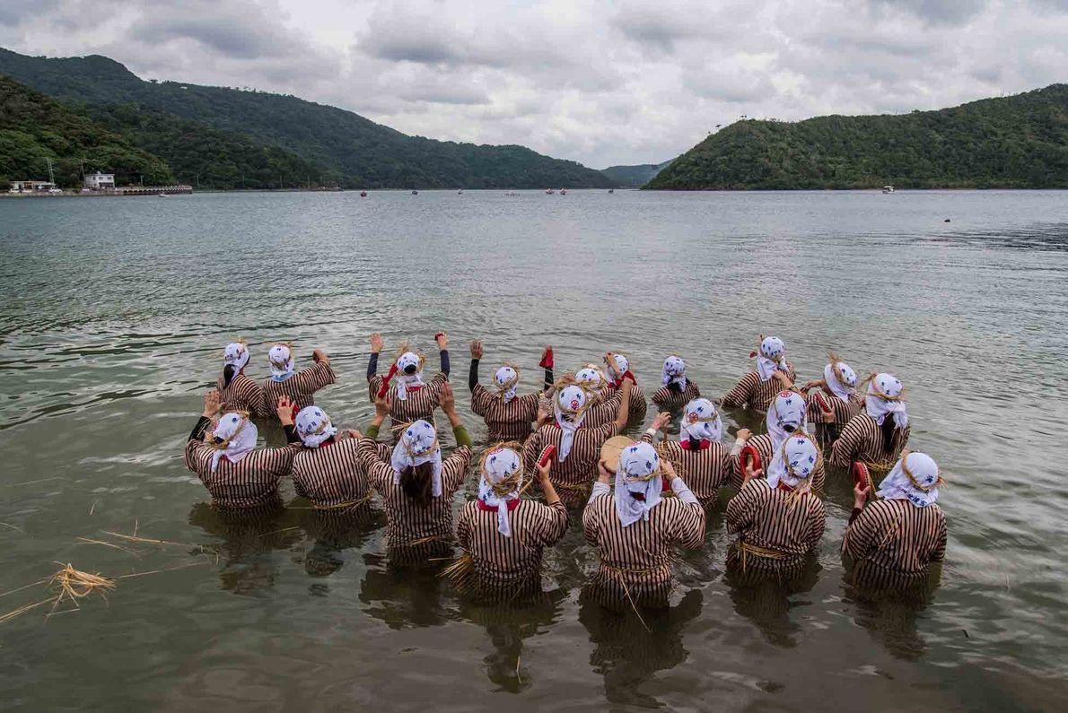 Pendant le festival de l'Ungami, les femmes se rendent dans la baie de Shioya pour accueillir ...