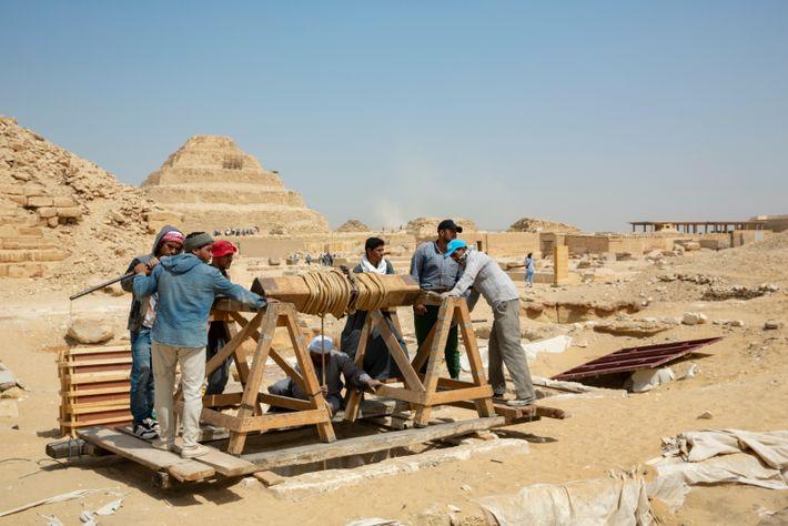 Les ouvriers descendent leur équipement vers l'atelier de momification et les tombes avec un treuil manuel. ...