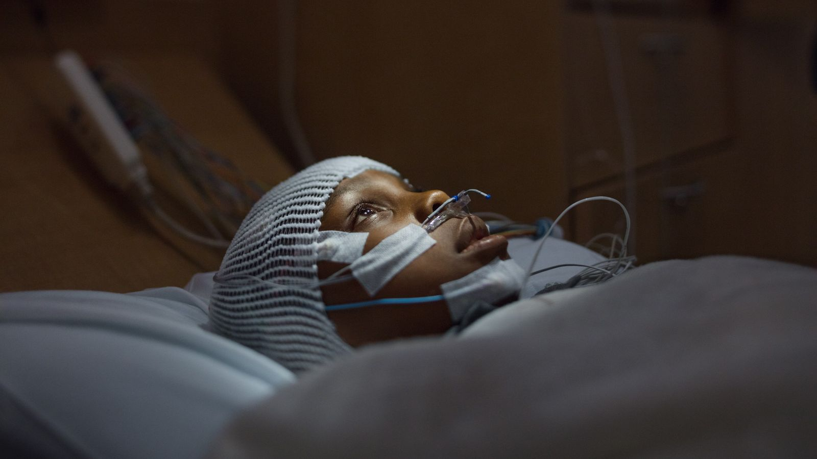 """Swathed in tubes and electrodes, 10-year-old Francis Ajua awaits """"lights out"""" at the Children's clinic. He ..."""