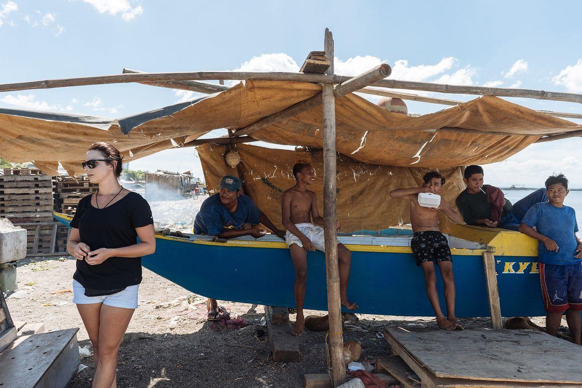Le long du fleuve Pasig, des hommes prennent une pause, tandis qu'un tour opérateur organise une ...
