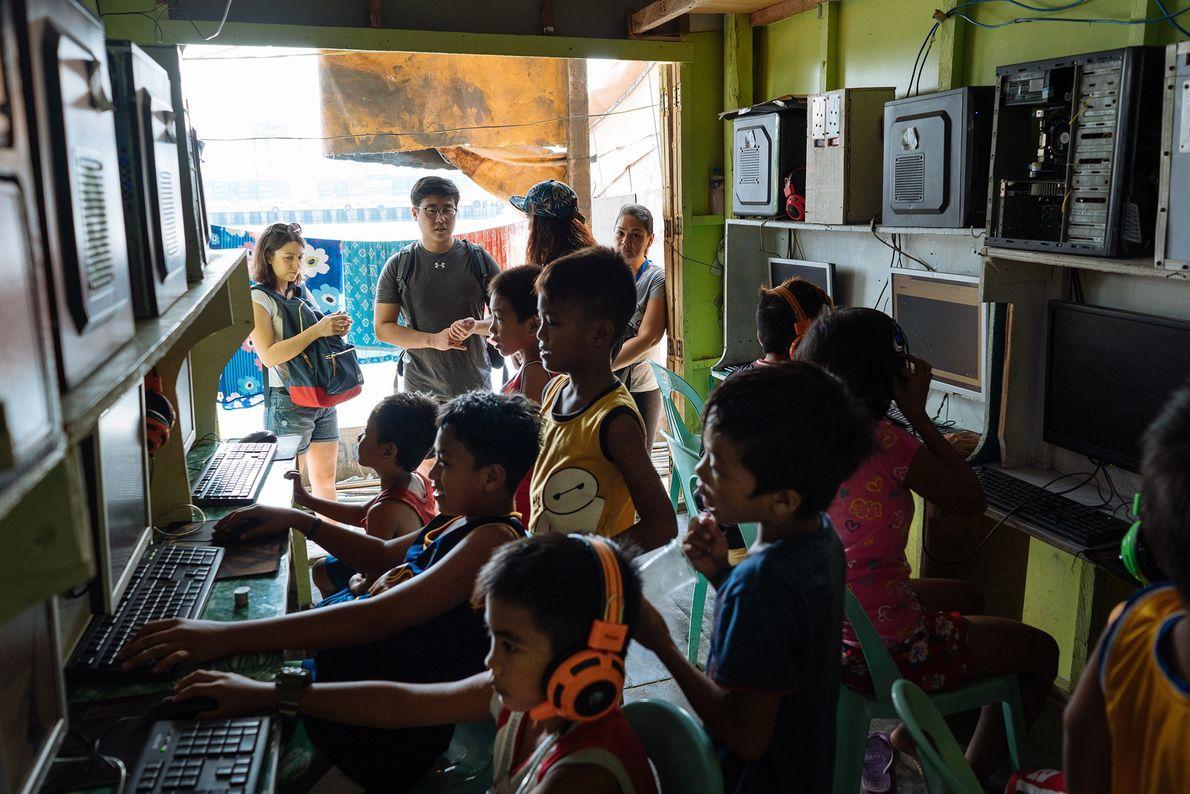 Dans le quartier de Tondo, à Manille, les enfants s'attroupent autour des ordinateurs d'un magasin.