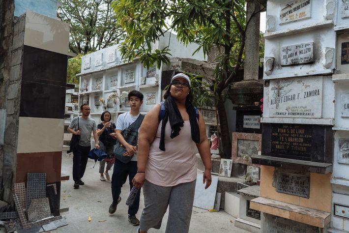 Des participants du Smokey Tours entrent dans la partie nord du cimetière de Manille, où vivent ...