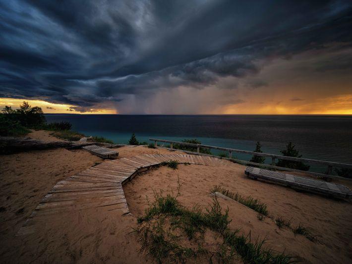 Au soleil couchant, un rideau de pluie tombe de nuages de tempête, non loin de Sleeping ...