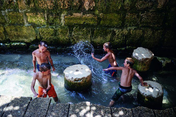 Des enfants jouent au débouché du tunnel d'Ézéchias, qui apporte l'eau jusqu'à ce bassin depuis la ...
