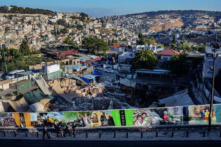 Un mur de photographies cache un ancien parking, où des archéologues ont mis au jour une ...
