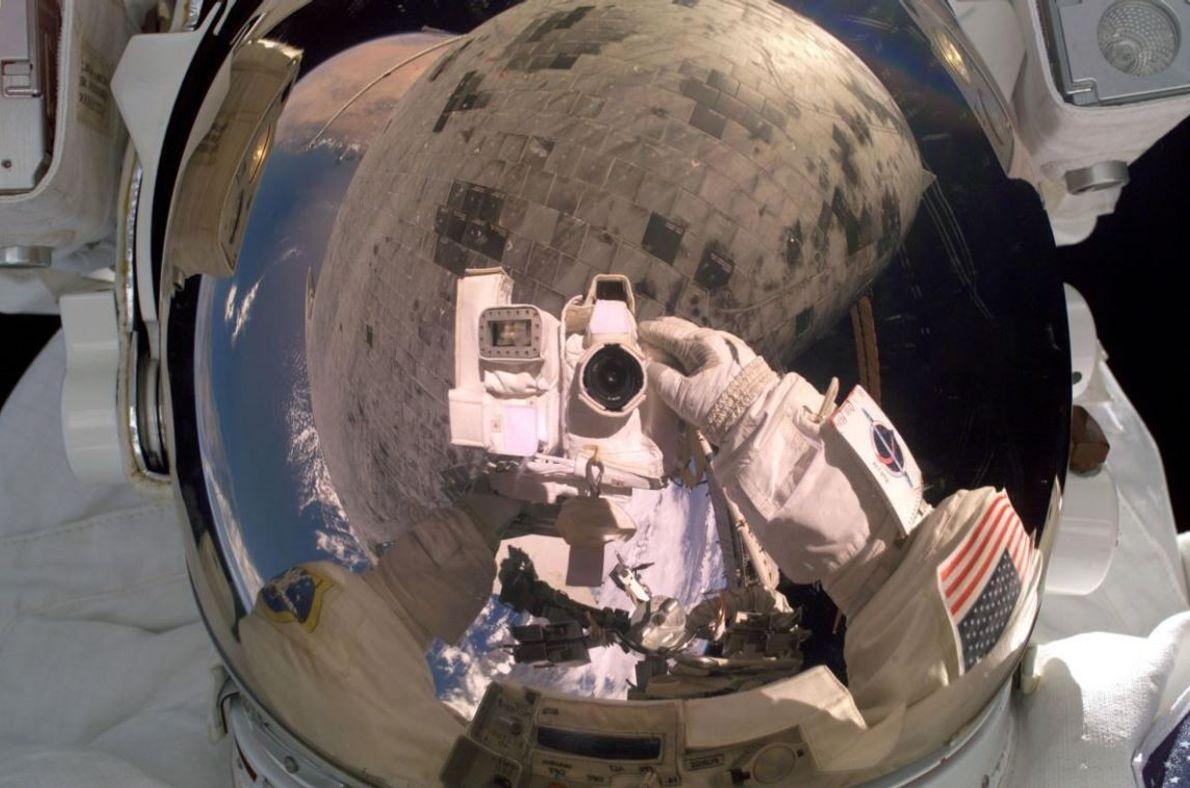L'astronaute Steve Robinson tourne la caméra vers lui lors d'une opération de maintenance sous la navette ...