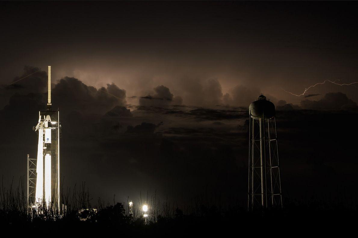 Un éclair illumine le ciel de Floride derrière la fusée Falcon 9, surmontée de la capsule ...