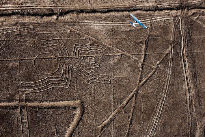 Un avion survole un ancien géoglyphe d'araignée dans le désert péruvien.