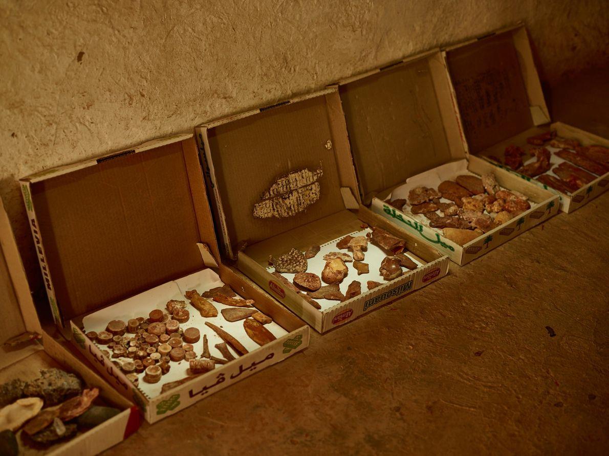 Des boîtes de pâtisseries sont remplies de fossiles et adossées au mur d'une maison près de Taouz, ...