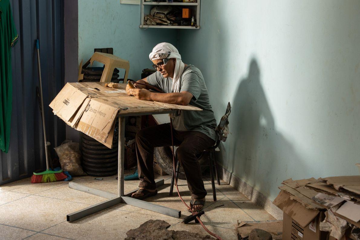 Mohand Ihmadi, propriétaire du centre Ihmadi Trilobites à Alnif, au Maroc, prépare une dent de Spinosaurus ...