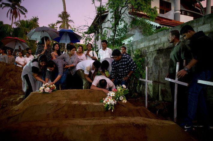 Des proches déposent des fleurs lors de l'enterrement de trois victimes de la même famille, victime ...