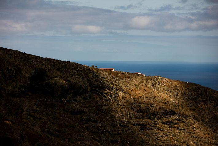 En fin d'après-midi, le soleil darde ses rayons sur une maison au sommet d'une falaise à ...