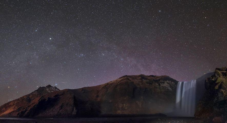 Des constellations, dont Orion et Persée, brillent au-dessus de la cascade de Skogafoss en Islande.