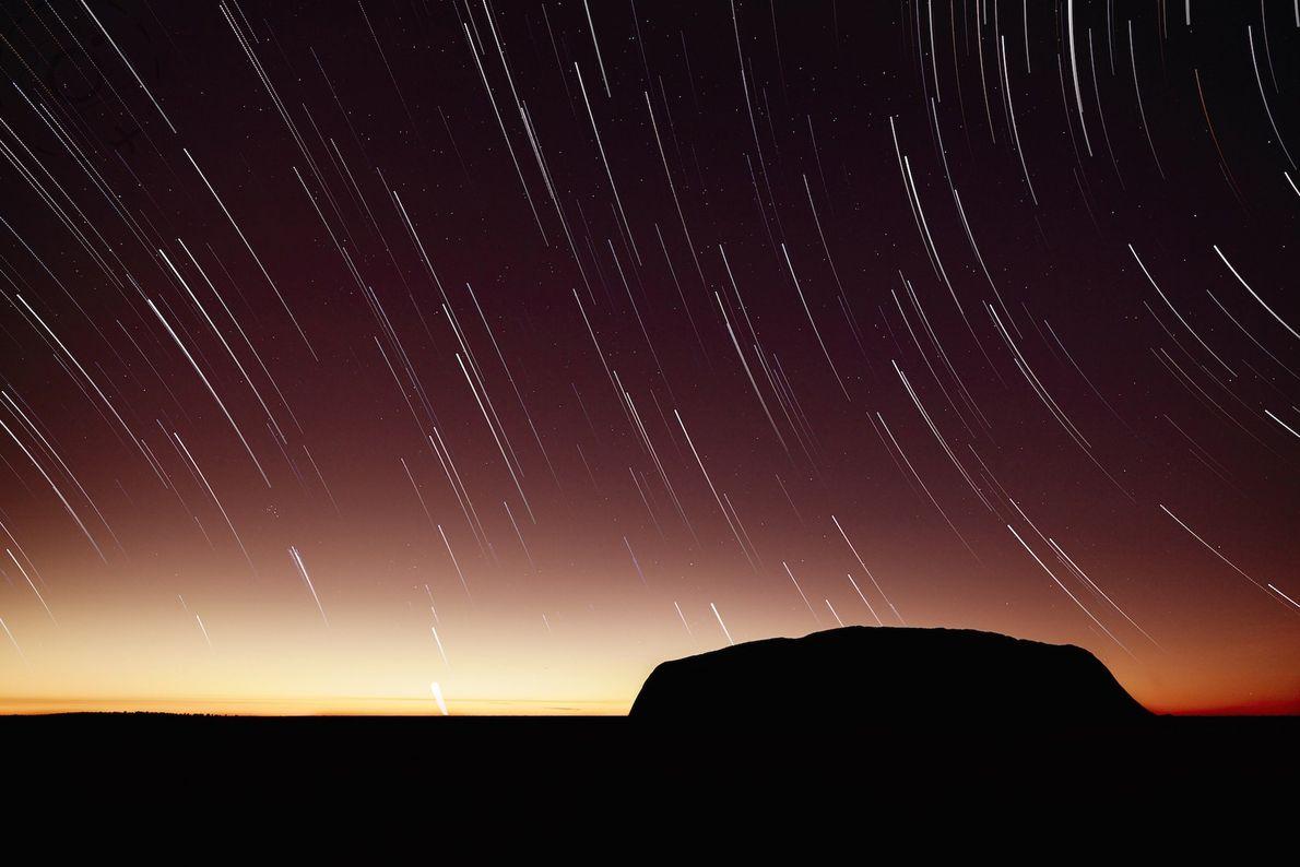 Une longue exposition au lever du soleil révèle les traînées d'étoiles surplombant Uluru.