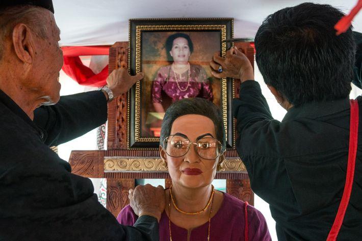 Des hommes accrochent une photographie de Sampe Rara' Tambing, décédée à l'âge de 79 ans, au-dessus ...