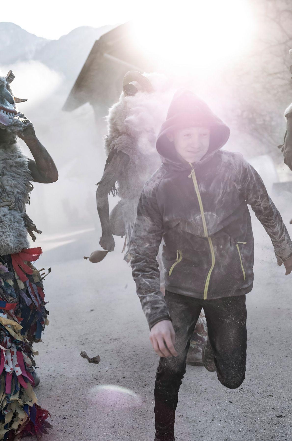 Les garçons du village portent des vêtements à capuche et manches longues pour se protéger de ...