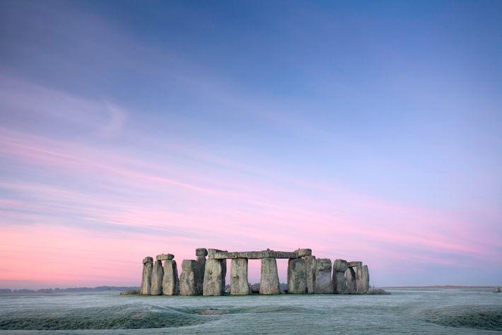 Des bandes de ciel roses et de pourpres se dessinent au-dessus de Stonehenge, à l'aube.