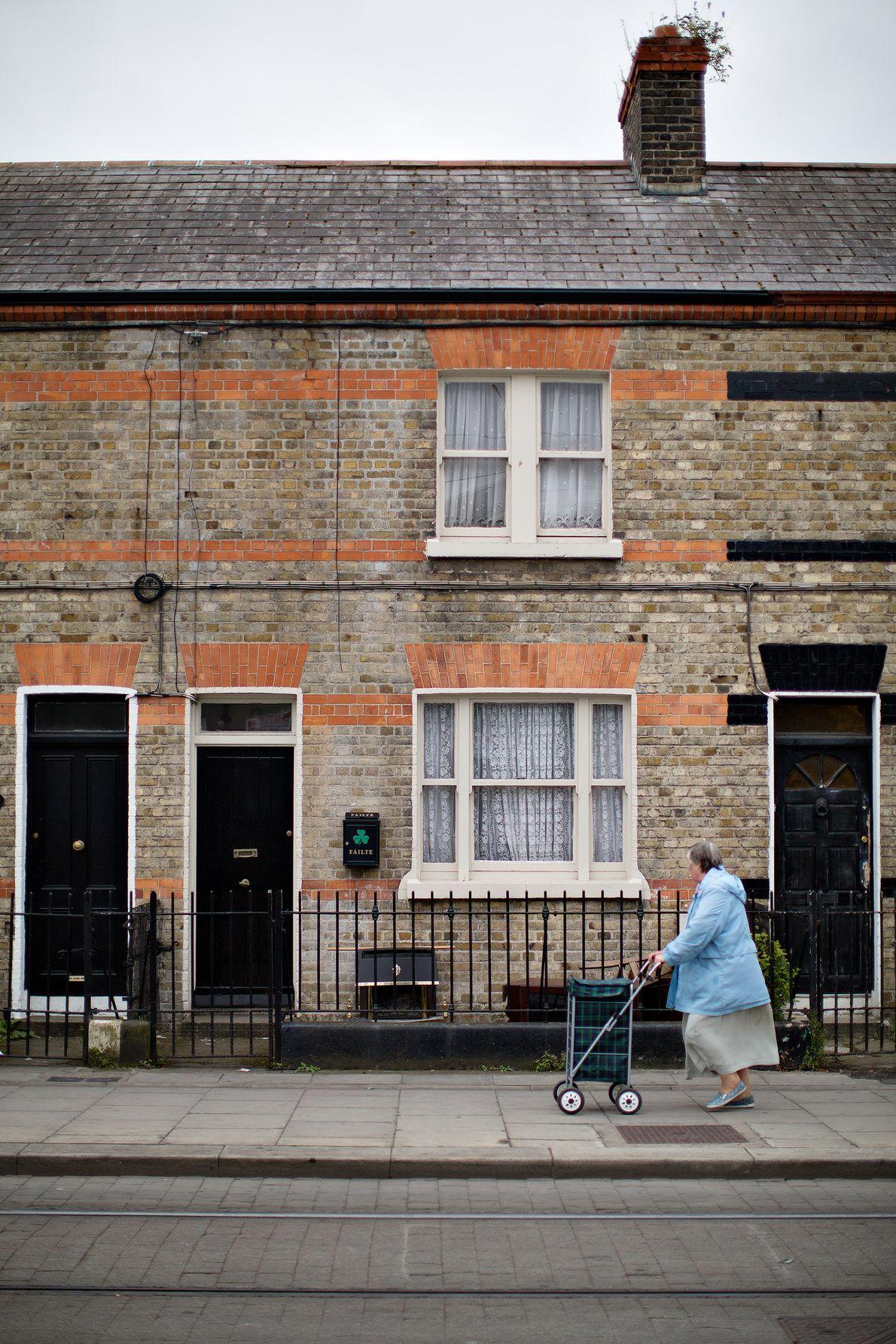 Une femme pousse un chariot dans les rues de Dublin. Le trèfle ou « sharmrock », ...