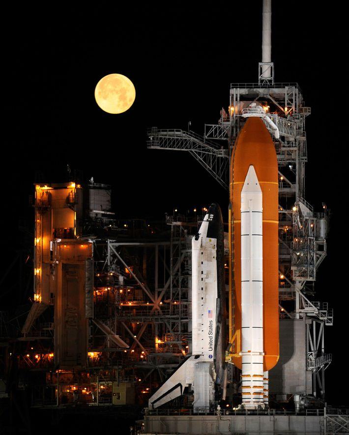 La pleine Lune s'élève au-dessus de la navette spatiale Discovery, installée sur la rampe de lancement ...