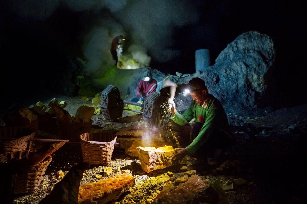 Des mineurs brisent les blocs de soufre à l'intérieur du cratère du volcan et remplissent des ...