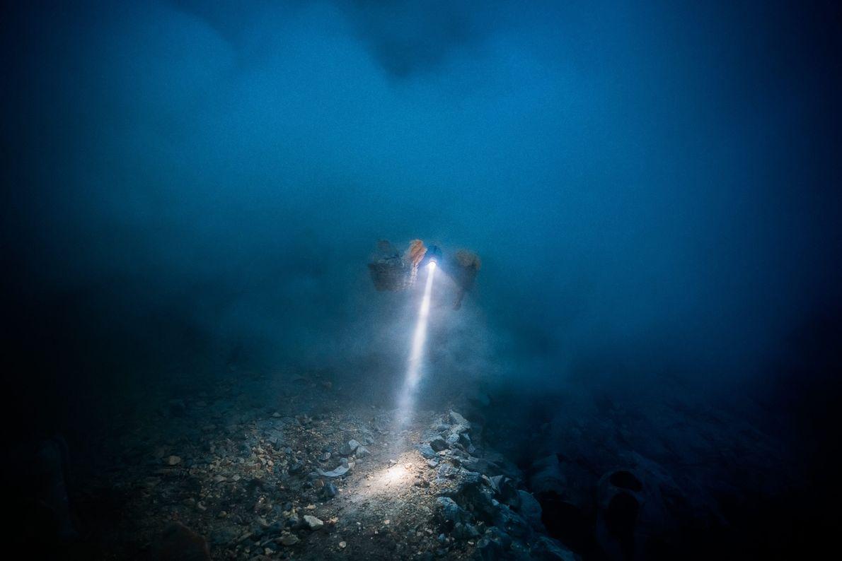 La lampe frontale d'un mineur perce l'obscurité et le gaz volcanique. Les mineurs commencent souvent leur ...
