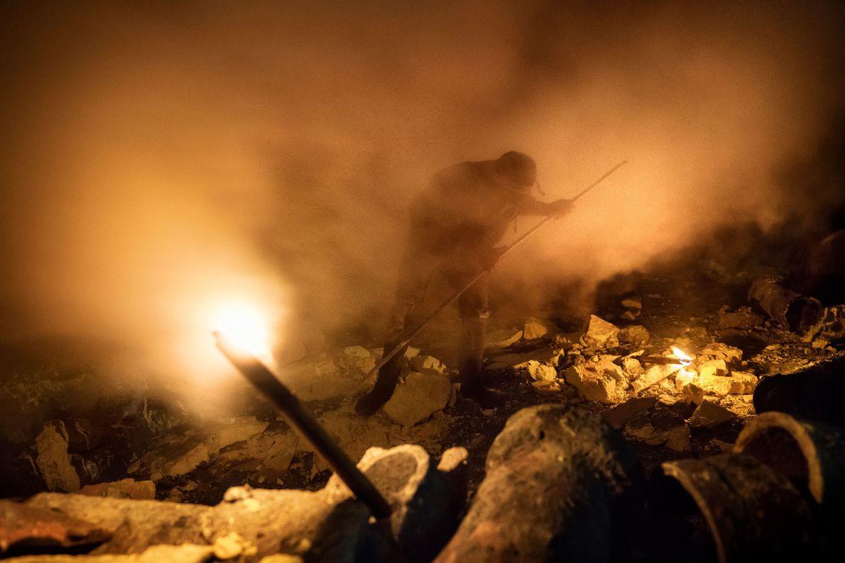 Pris dans le gaz sulfurique, un mineur utilise un poteau métallique pour extraire des morceaux de ...