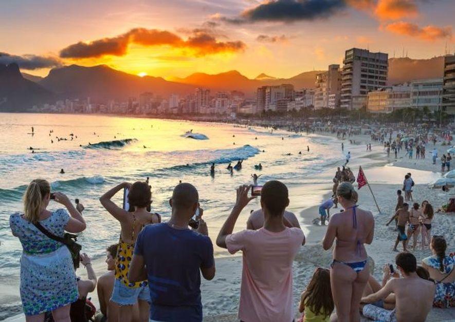 Des touristes prennent en photo le coucher du soleil sur la plage d'Ipanema à Rio de ...
