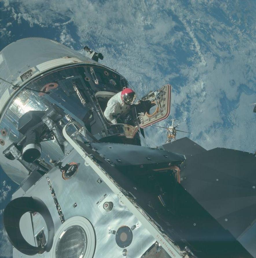 En orbite au-dessus de la Terre, l'astronaute Dave Scott entame une sortie en-dehors du module de ...