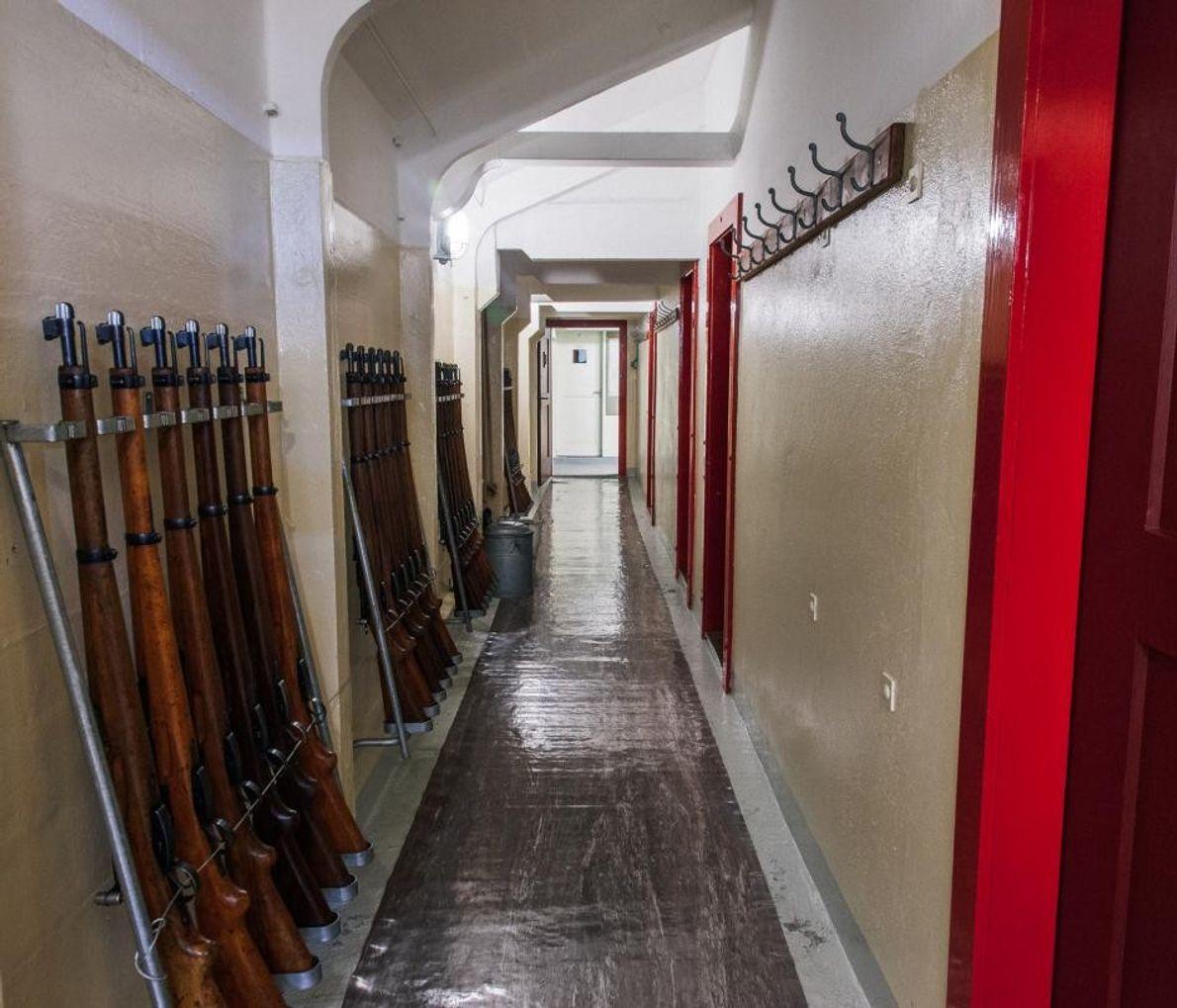Couloir avec, à gauche, des carabines alignées, Fort Waldbrand
