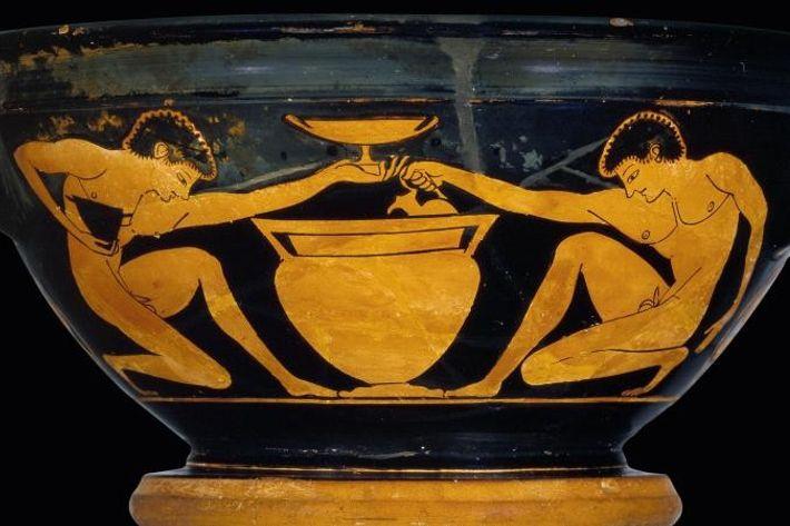 Deux jeunes hommes nus, représentés sur une coupe du 6e siècle avant J.-C., servent du vin ...