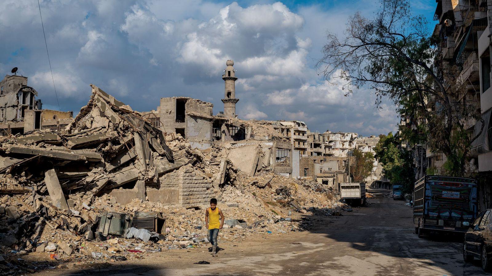 Un garçon se promène devant une ancienne école et une mosquée dans le quartier de Sukkari, ...