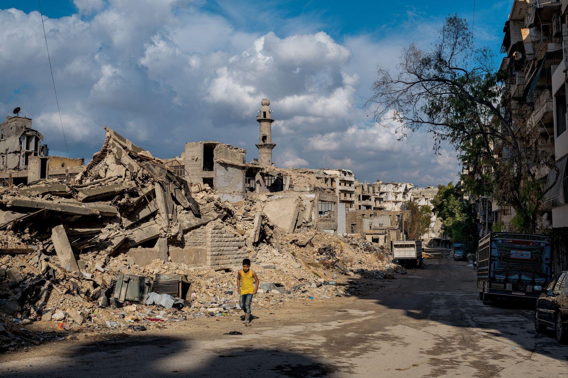 Un garçon se promène devant une ancienne école et une mosquée dans le quartier de Sukkari, dans le sud d'Alep. La mosquée est en cours de reconstruction ; la plupart des bâtiments environnants resteront à l'état de ruines quelques temps encore.