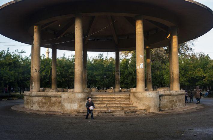 Un garçon joue avec un ballon de football devant un kiosque dans le parc public d'Alep, ...