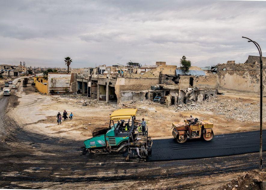 Près de l'aéroport international dans le quartier de Karm al Jazmati, à l'est d'Alep, les ouvriers construisent une route pour remplacer celle qui a été détruite.