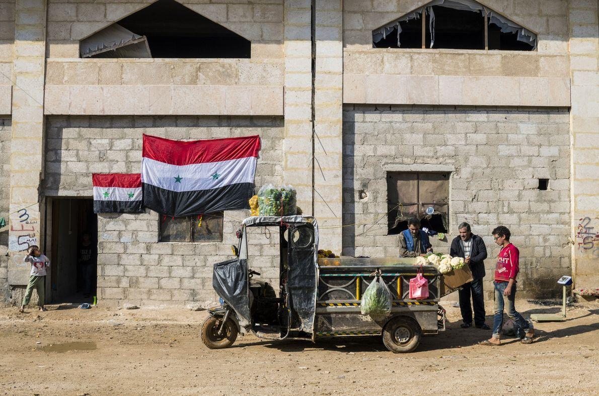Un vendeur de rue tente de vendre ses légumes à un homme déplacé de l'est d'Alep, …